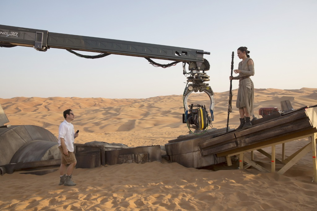 J.J. Abrams and Daisy Ridley standing on set in a dessert speaking