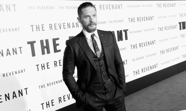 Tom Hardy wears a black suit on a red carpet.