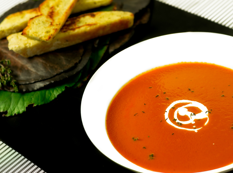 roasted red pepper and tomato soup in a white bowl with bread