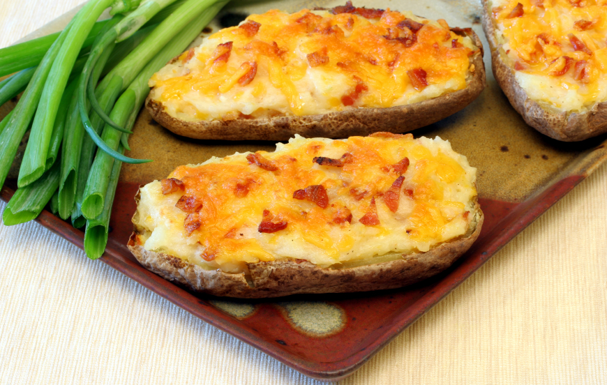two twice baked potatoes with bacon and cheddar cheese