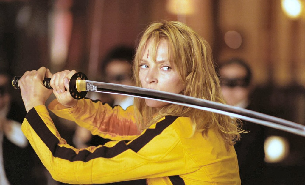 Uma Thurman in a yellow jumpsuit, holding a sword parallel to the ground across her shoulder