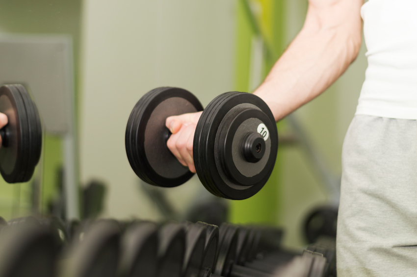 man picks up a dumbbell from a rack