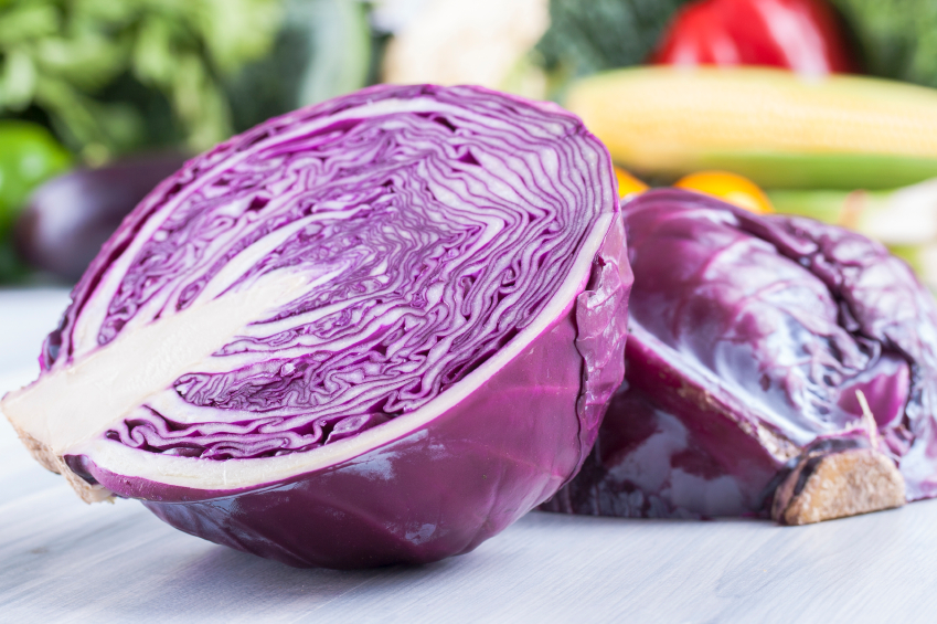 head of red cabbage cut in half on a cutting board