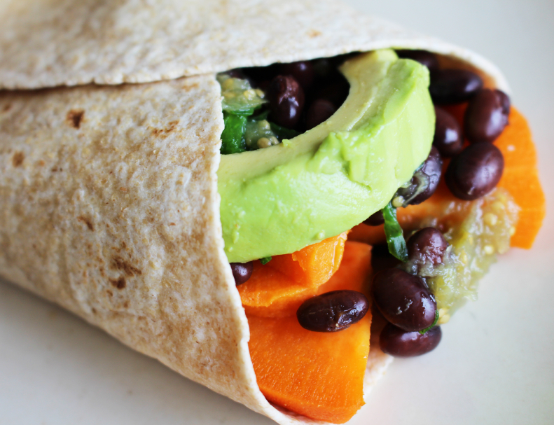 close up of a burrito filled with avocado, black beans, and sweet potato