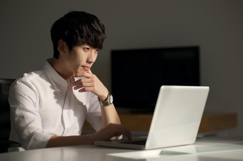 Man at desk looking at computer