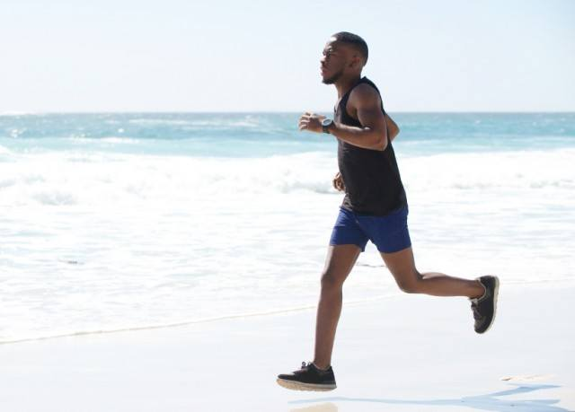 A young African-American man runs on the beach