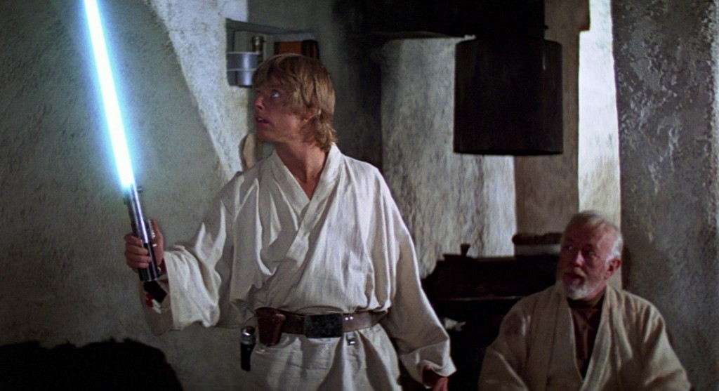Luke Skywalker tries out a lightsaber as Obi-Wan Kenobi watches.