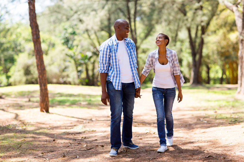 cheerful African American couple walking and looking at each other