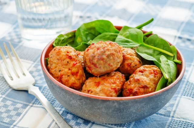 meatballs with red pepper sauce and spinach in a bowl