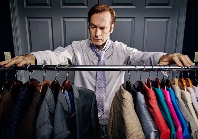 Saul stands in front of a rack filled with suits.