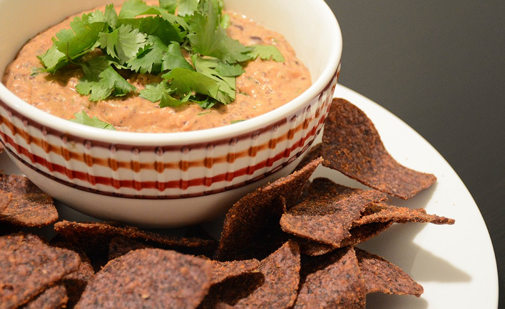 creamy black bean dip in a bowl with blue corn tortilla chips and cilantro