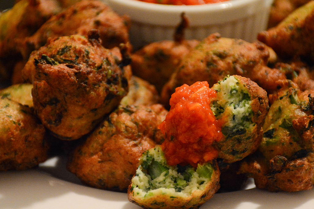 close shot of broccoli rabe-ricotta fritters with tomato-basil sauce