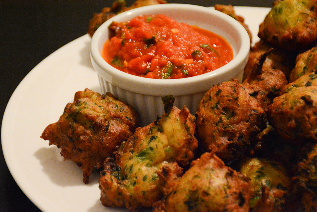 white plate of broccoli rabe-ricotta fritters and a side of tomato-basil sauce