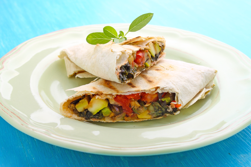 burrito with grilled vegetables and sauce on a white plate