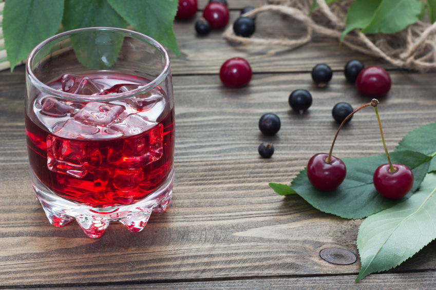 iced cherry drink on a wooden table with berries