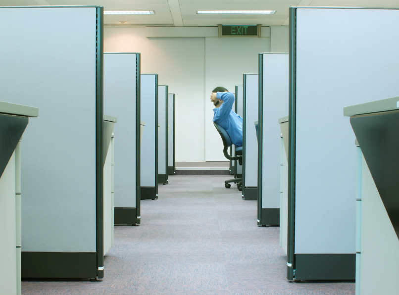 man in empty row of cubicles