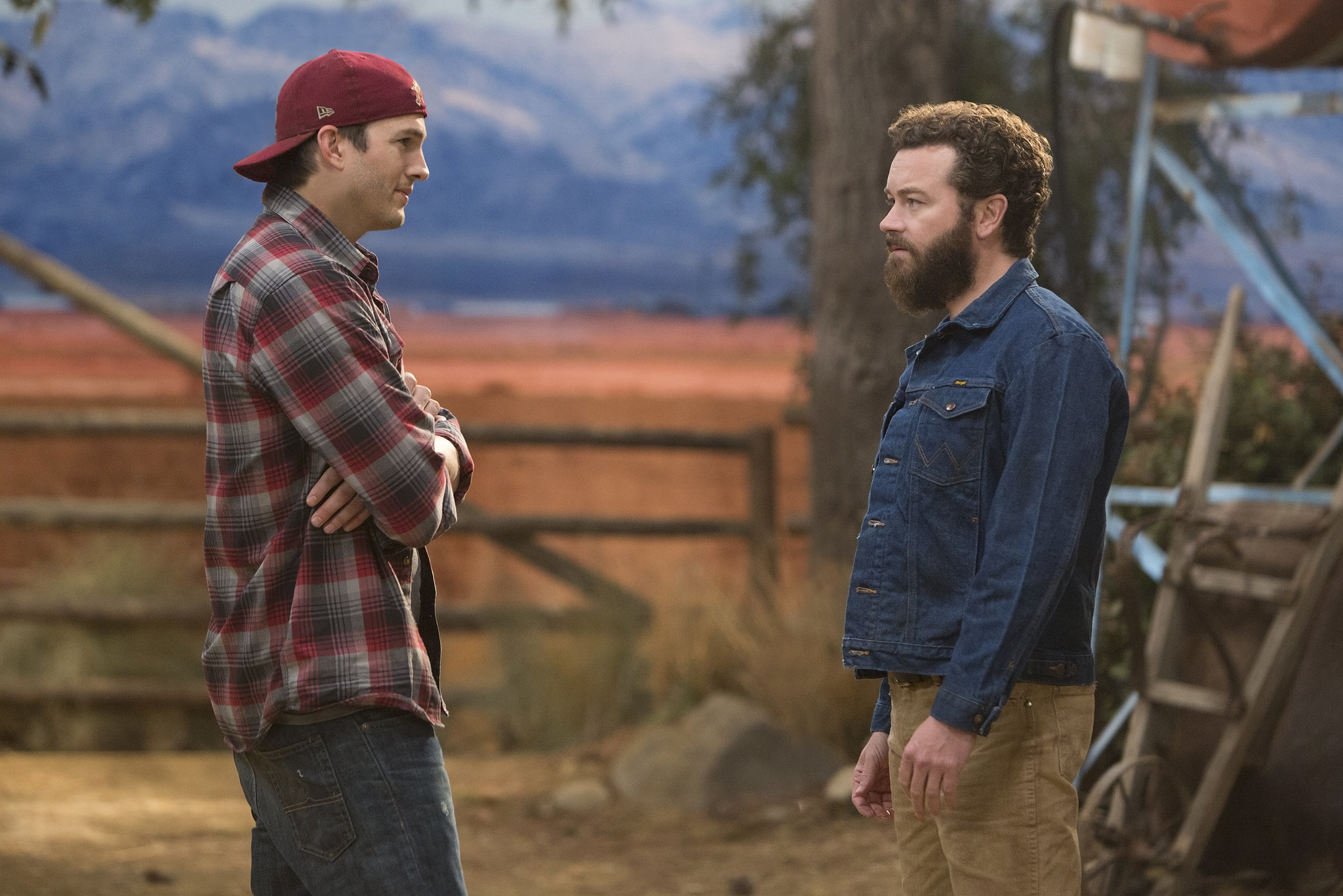 Ashton Kutcher and Danny Masterson talk to each other outside in The Ranch