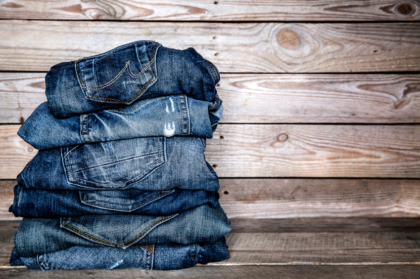 pile of six jeans on a wooden background