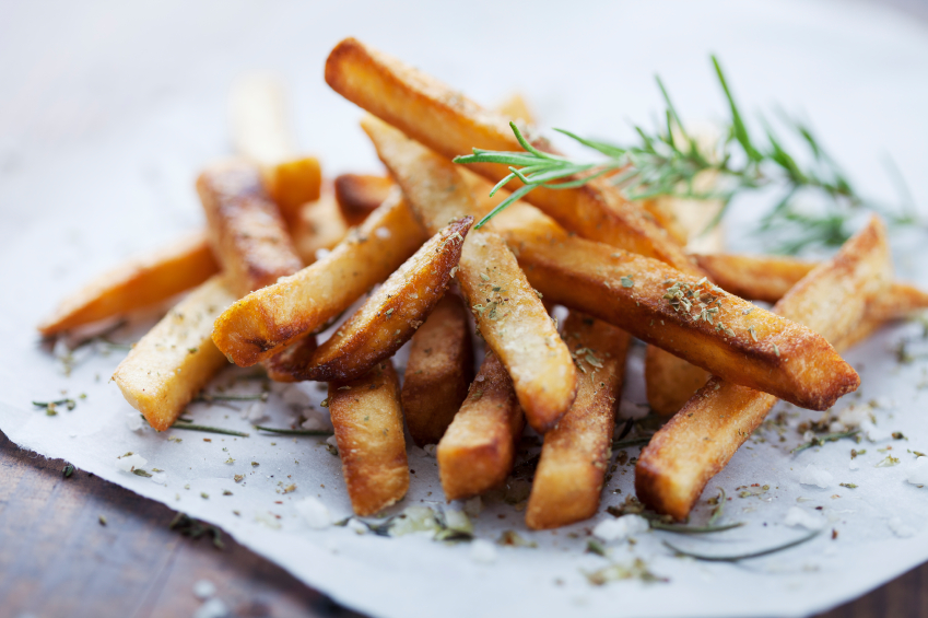 close up of french fries with salt and rosemary on a parchment sheet