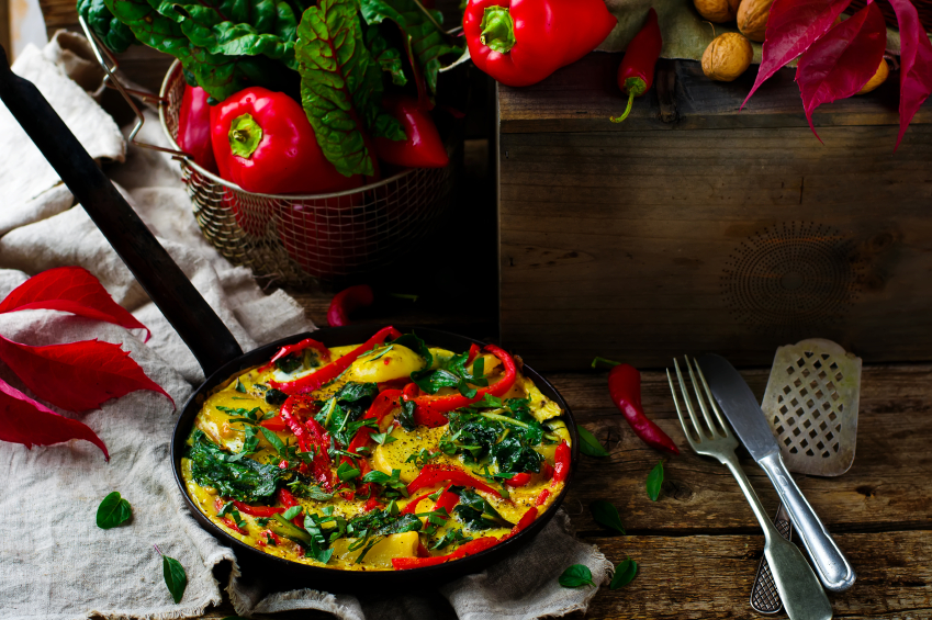 black steel skillet with potato, pepper, and greens frittata