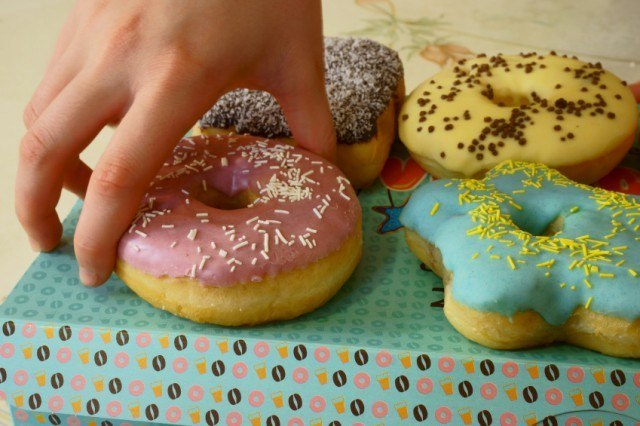 A man grabs a pink glazed donut with white sprinkles from a table