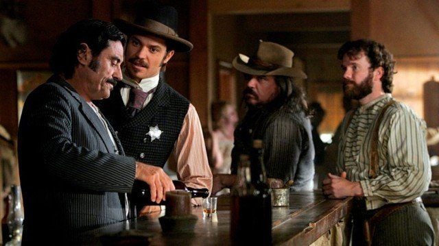 A group of men having a drink at a bar in 'Deadwood'.
