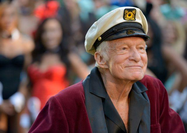 Hugh Hefner in a red robe and captain's hat