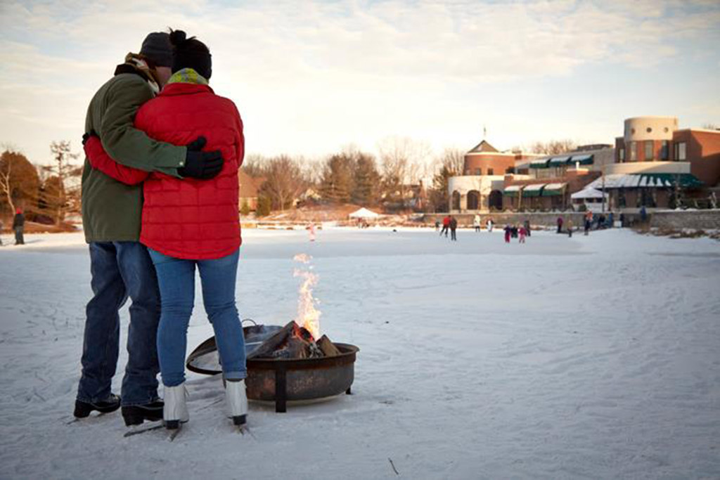 Couple warming up by the fire after ice skating at The American Club in Kohler, Wisconsin