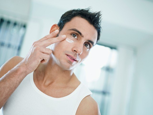 man putting a sulfur treatment on his face