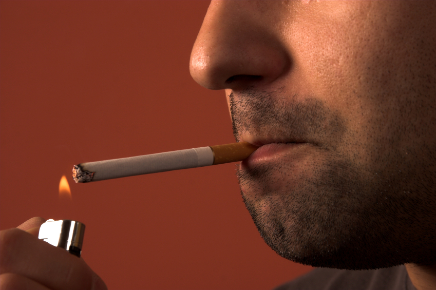 man lights a cigarette in his mouth