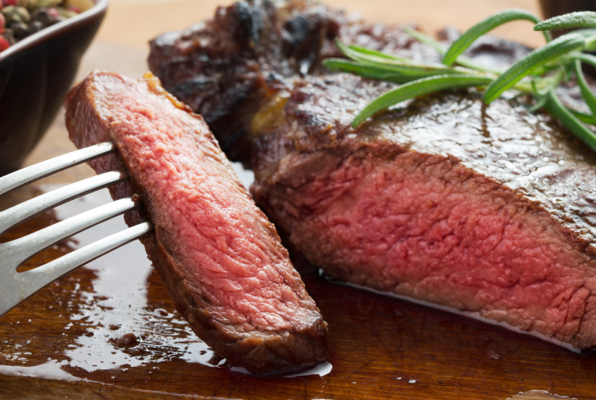 close up of slicing a medium rare steak