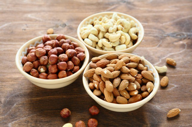 bowls of almonds, hazelnuts, and cashews sitting on a wooden counter