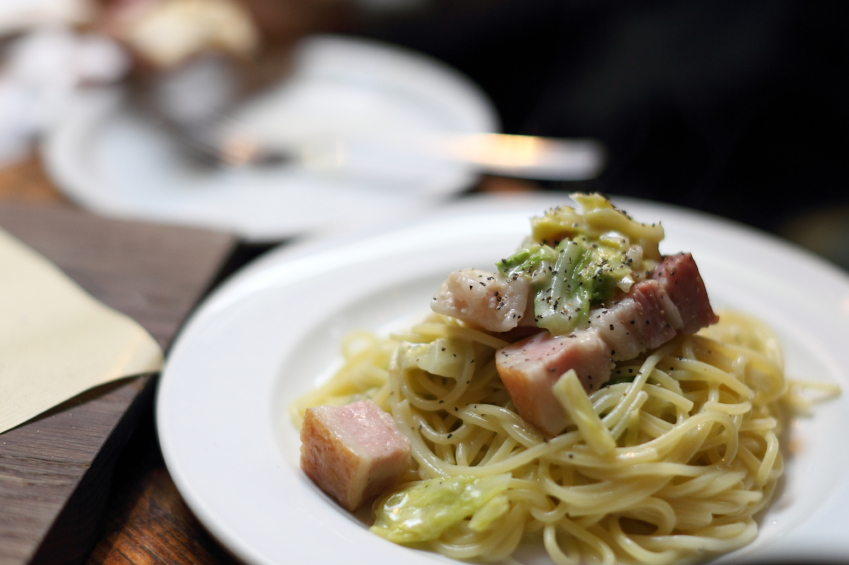 close shot of a plate of pasta with bacon and cabbage