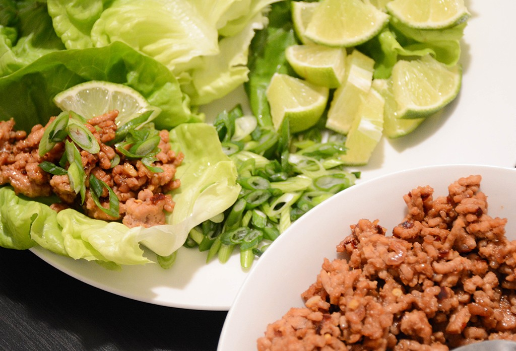 soy-ginger pork lettuce wraps assembly with meat and garnishes