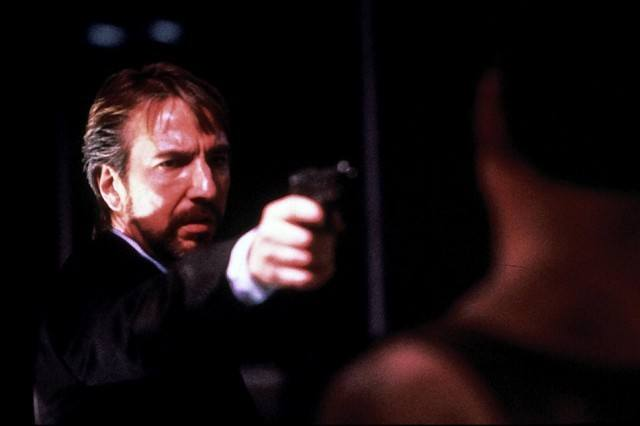 Hans Gruber is pointing a gun at John McClane.