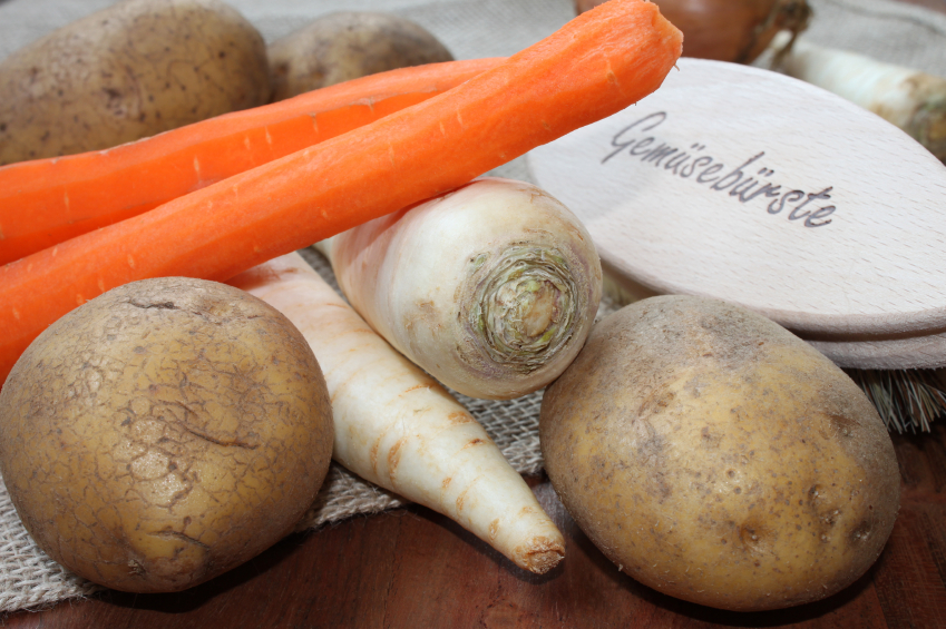 assorted root vegetables including parsnips, potatoes, and peeled carrots