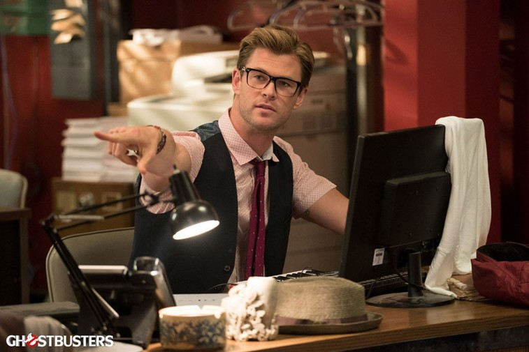 Chris Hemsworth is sitting at a desk and wearing glasses.