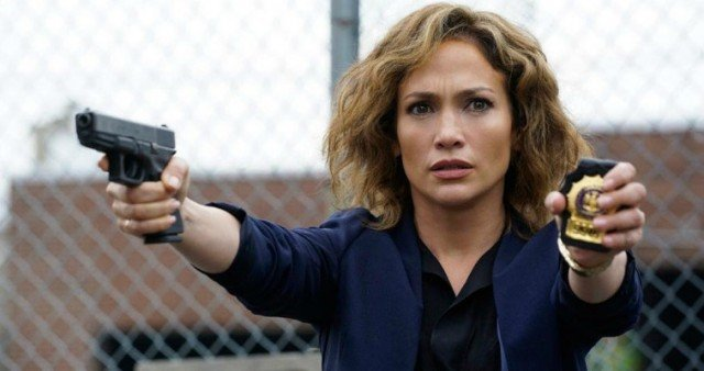 Jennifer Lopez holding a gun and badge in 'Shades of Blue'.