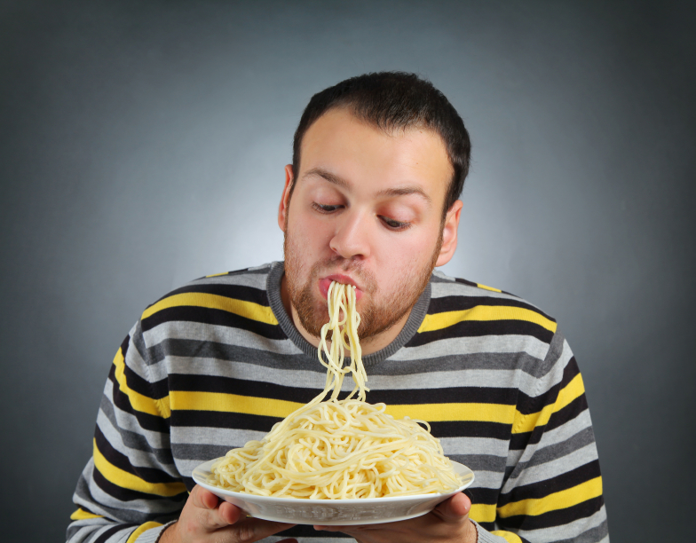 man slurping a huge plate of spaghetti without a fork