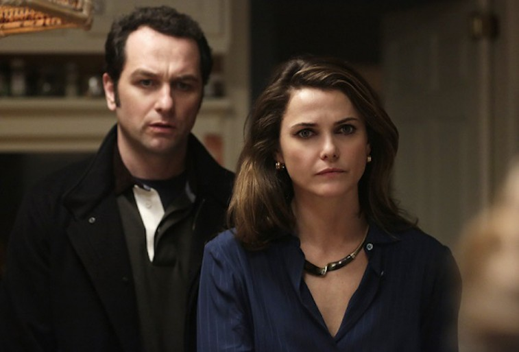 Keri Russell stands in front of Matthew Rhys in a scene