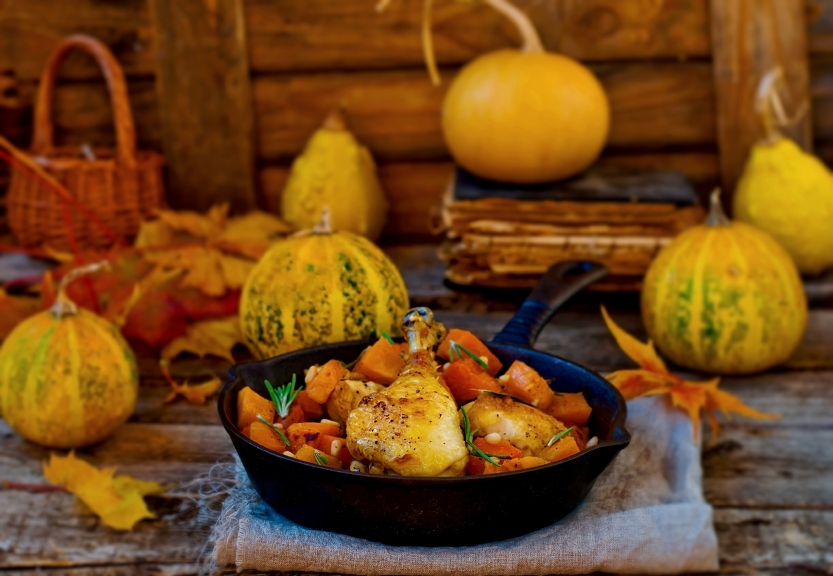 cast-iron skillet filled with roast chicken and pumpkin
