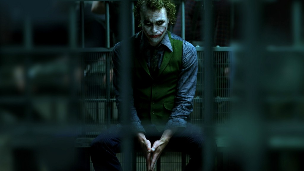 Heath Ledger as the Joker, sitting in a jail cell with his hands together