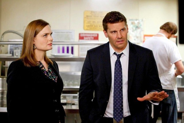 Emily Deschanel and David Boreanaz stand in a kitchen during an investigation in a scene from Bones