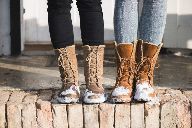 Two women wearing boots covered in snow
