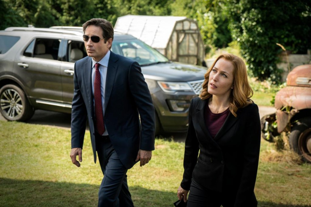 Mulder and Scully walk on grass in front of a car