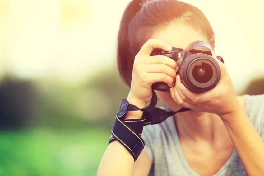 young woman taking photo with camera