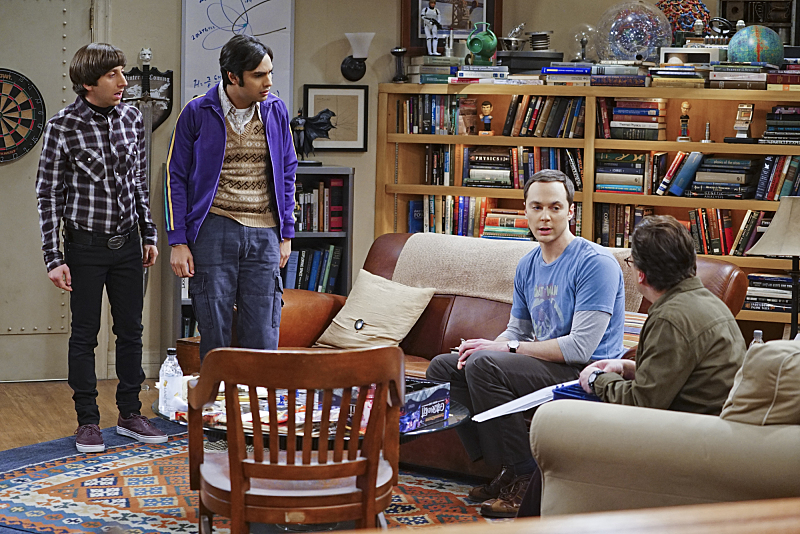 The men of the Big Bang Theory sit and stand in a living room