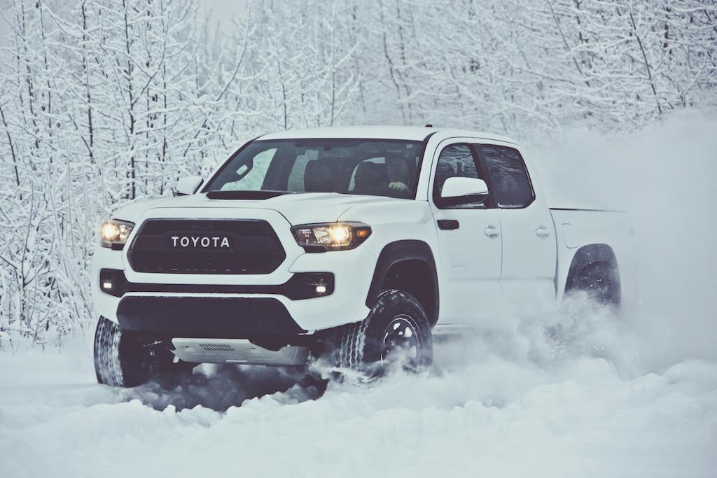 White Toyota Tacoma driving through snow.