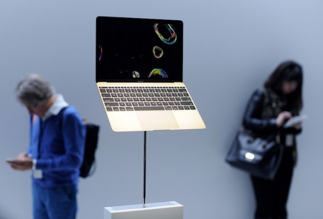 A Macbook Air on display with people texting in the background.