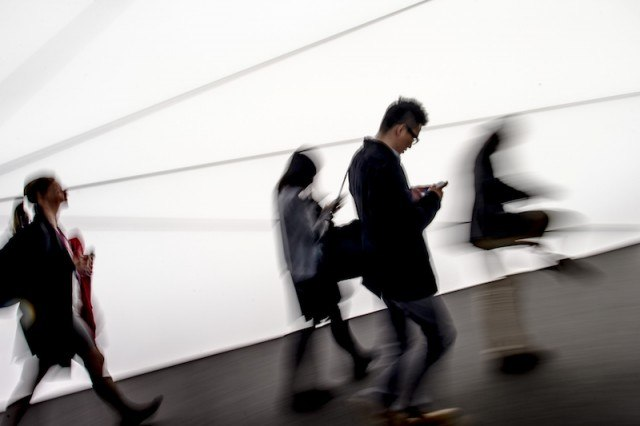 People walking with man using smartphone